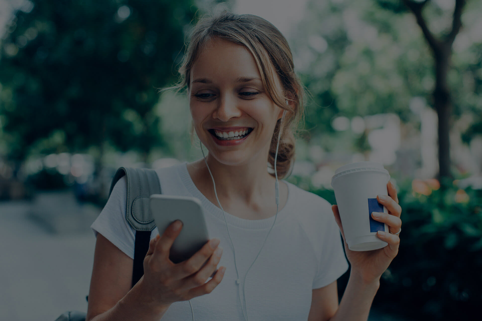 Smiling woman holding coffee and phone