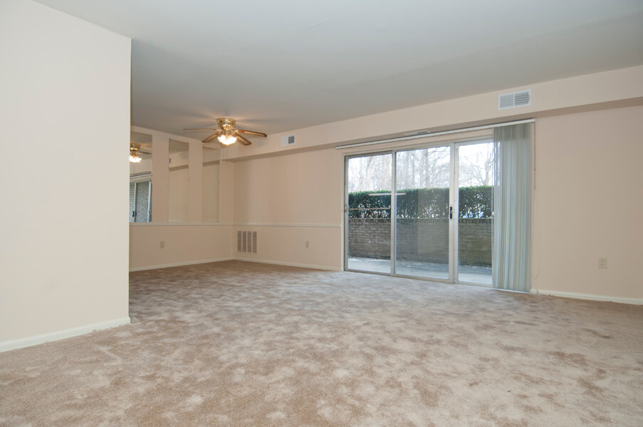 Large carpeted living/dining room at Auden Place with sliding doors to terrace