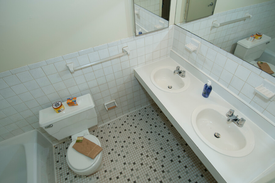 Auden Place bathroom with double sink and tile floor