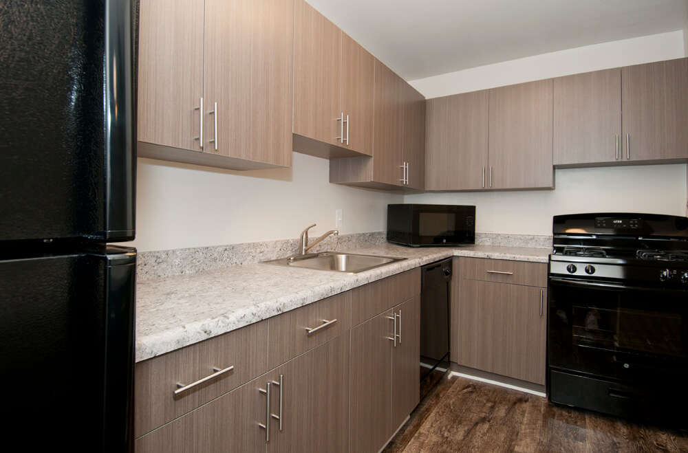 Auden Place kitchen with wood like floors, mid-tone wood cabinets and black appliances