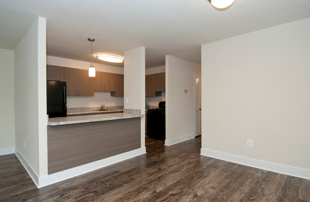 Auden Place living/dining room with wood like floors and pass through kitchen with wood cabinets and black appliances
