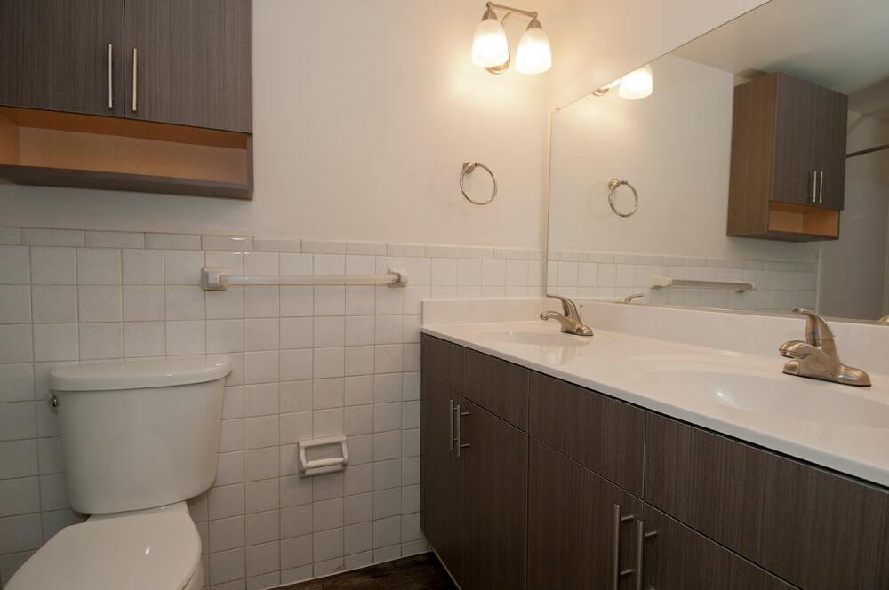 Auden Place bathroom with tiled wall, espresso cabinets and double sink